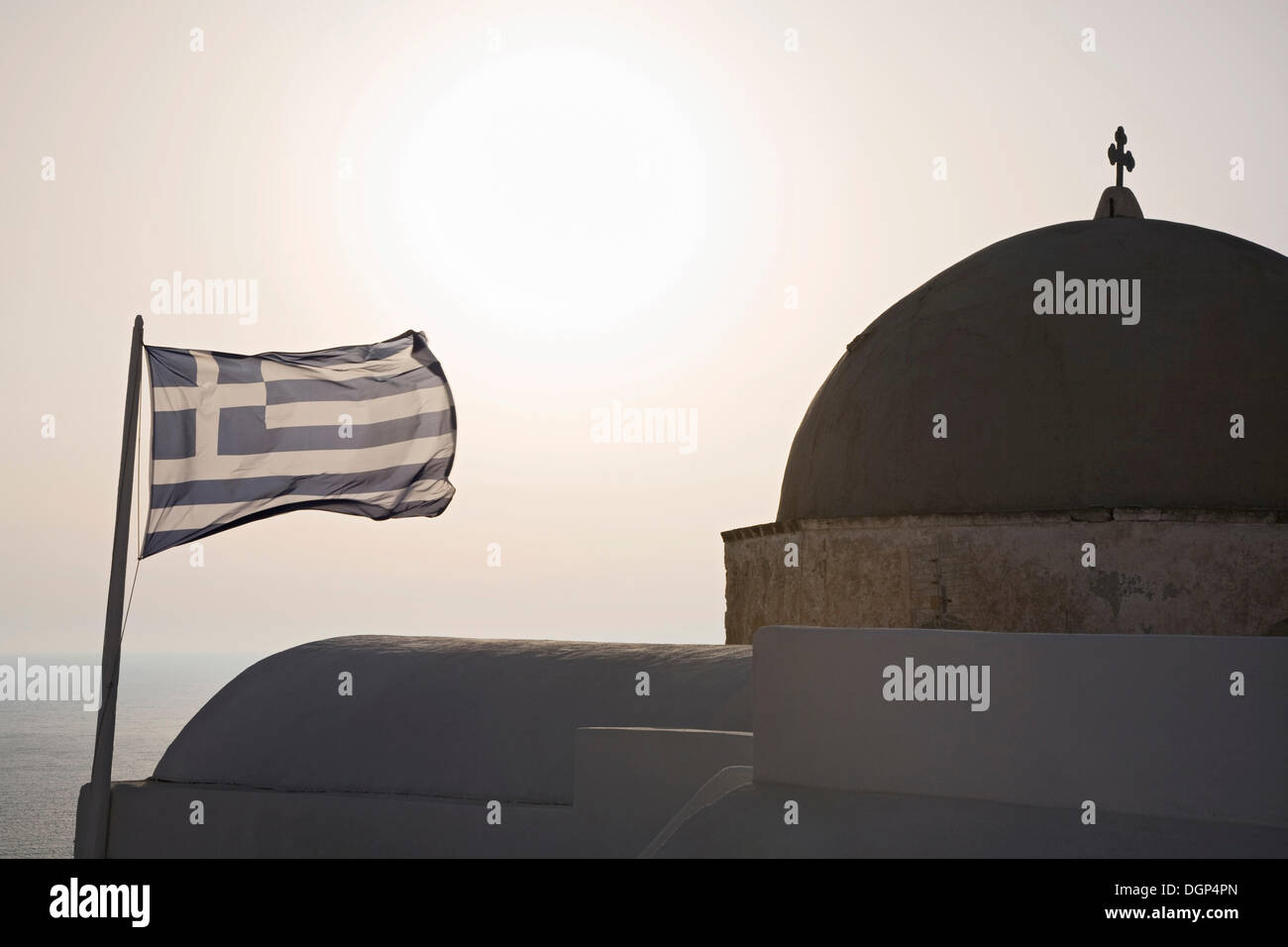 Greek flag beside the cupola of a church, Oia, Santorini, Cyclades, Greece, Europe - Stock Image