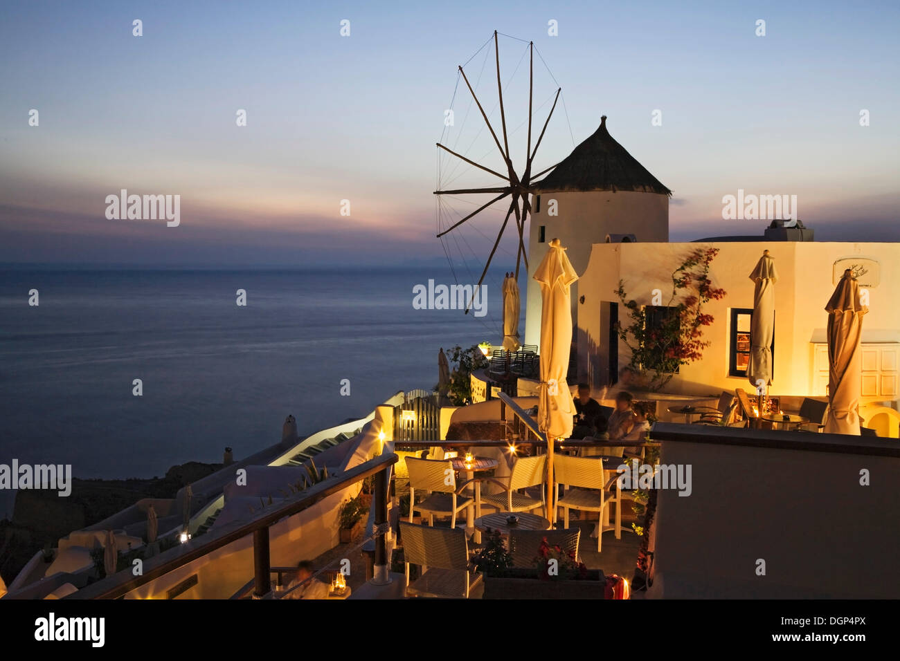 Guests enjoying the sunset on a terrace of a restaurant, Oia, Santorini, Cyclades, Greece, Europe - Stock Image