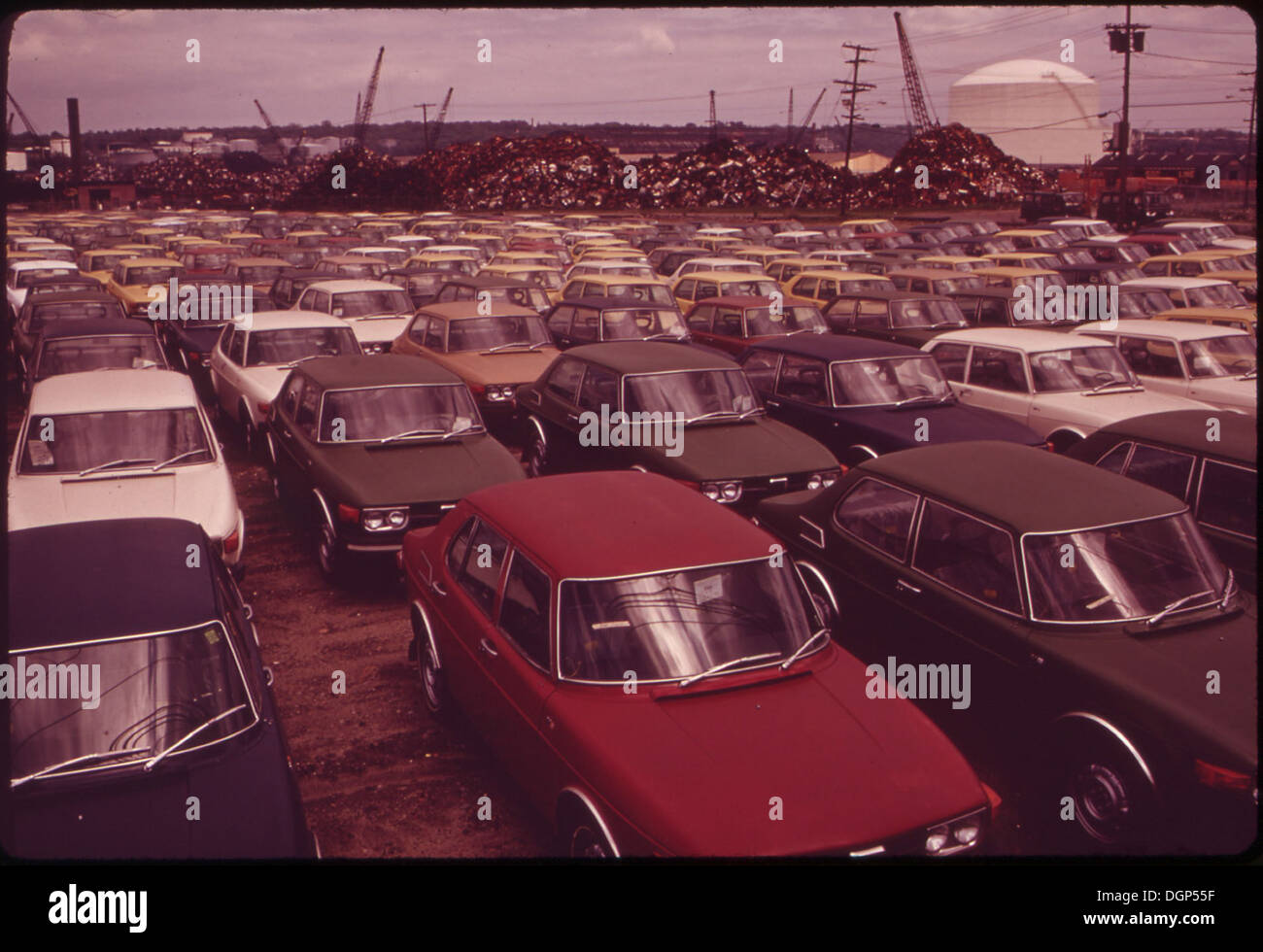 NEW CARS, AND SCRAP METAL FROM OLD CARS (IN BACKGROUND) READY FOR ...