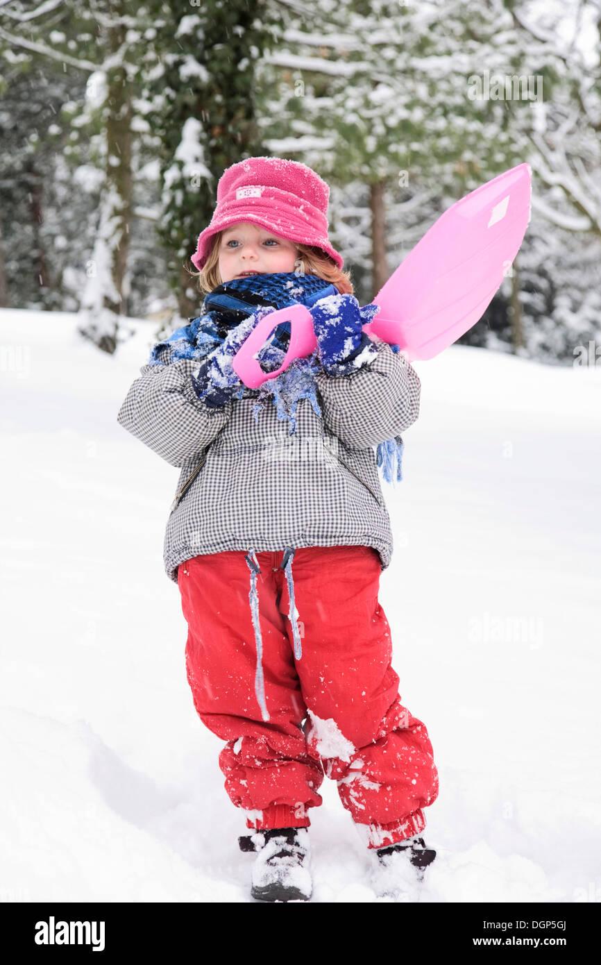 Little girl shouldering her sled - Stock Image