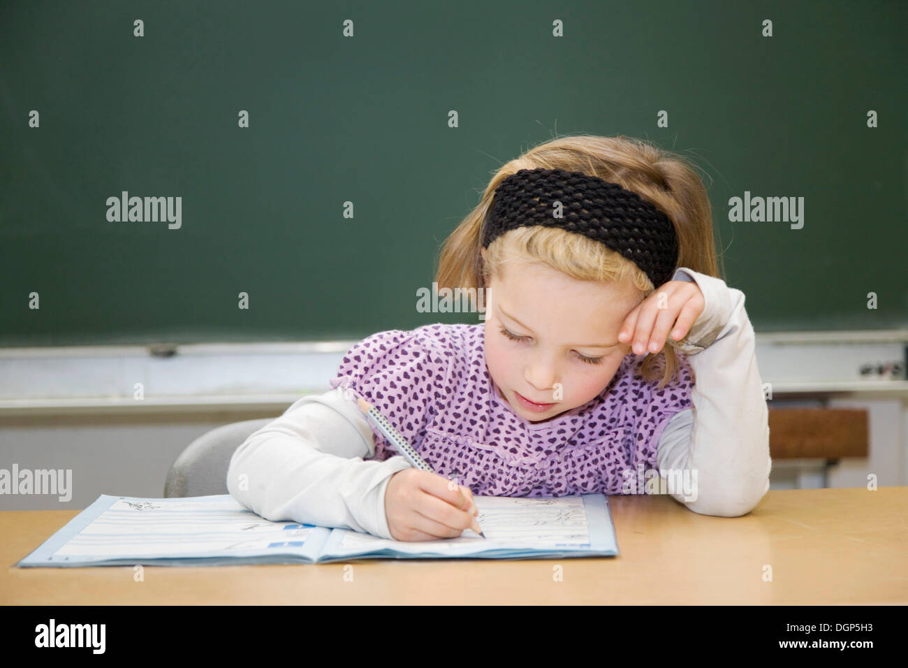 Girls focused on writing during class - Stock Image