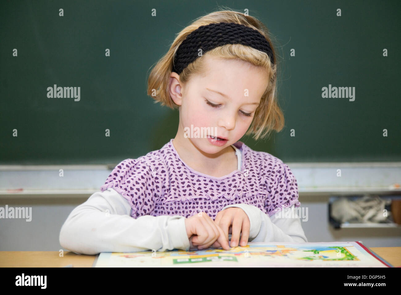 Girls focused on reading during class - Stock Image