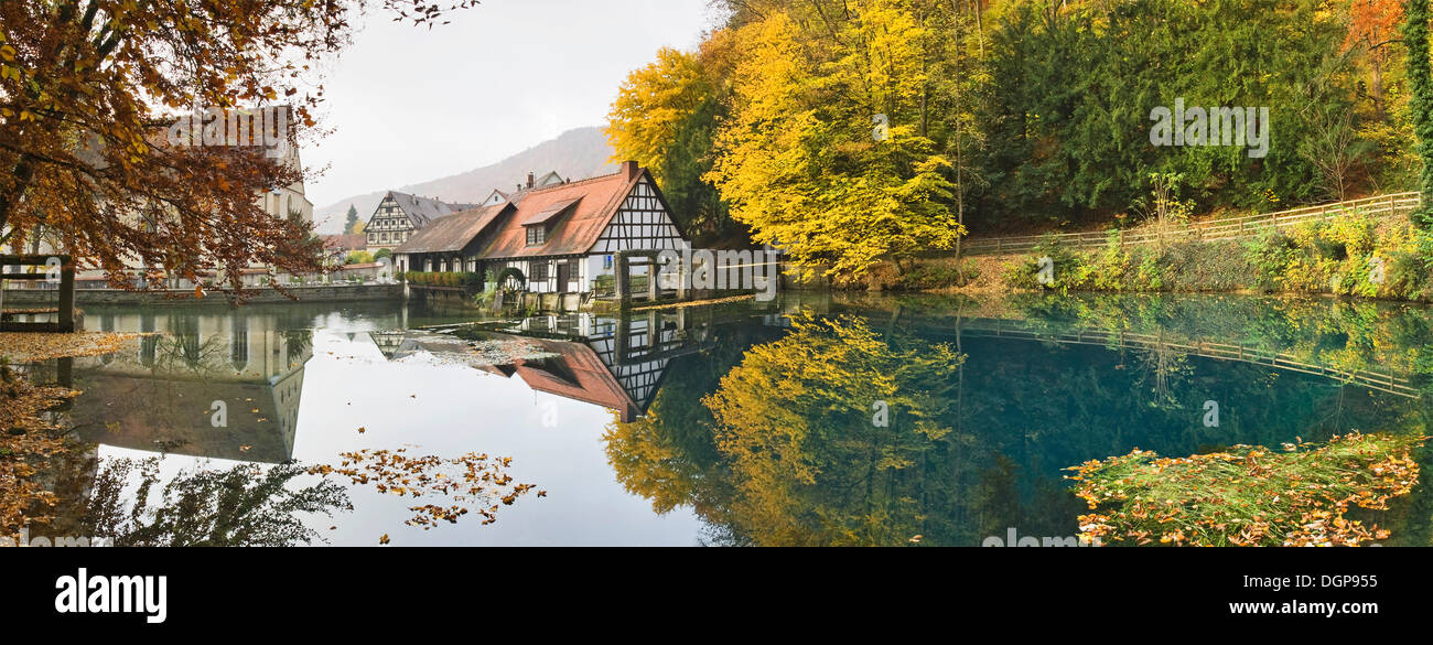 Blaubeuren Abbey and the mill being reflected on the Blautopf karstic spring, Swabian Alps, Baden-Wuerttemberg - Stock Image