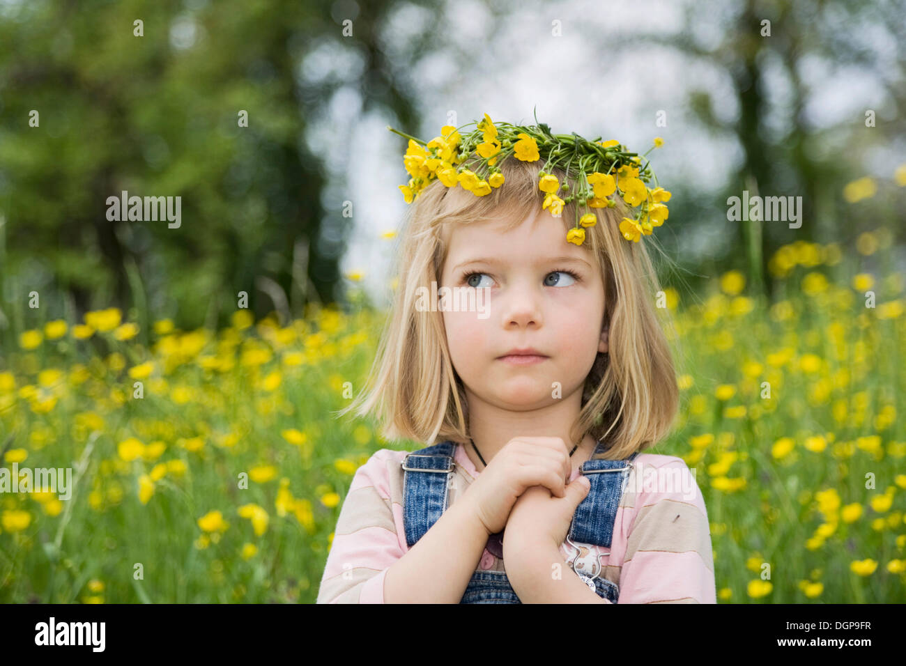 Girl wearing a floral wreath on her head, with clasped hands and a questioning look, portrait - Stock Image
