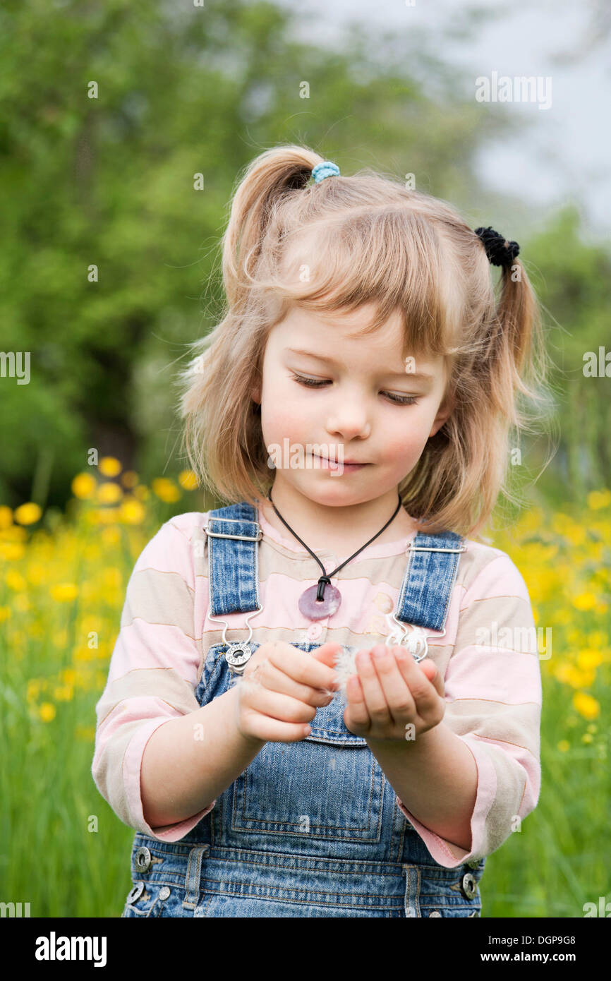 Girl walking through a flower meadow - Stock Image