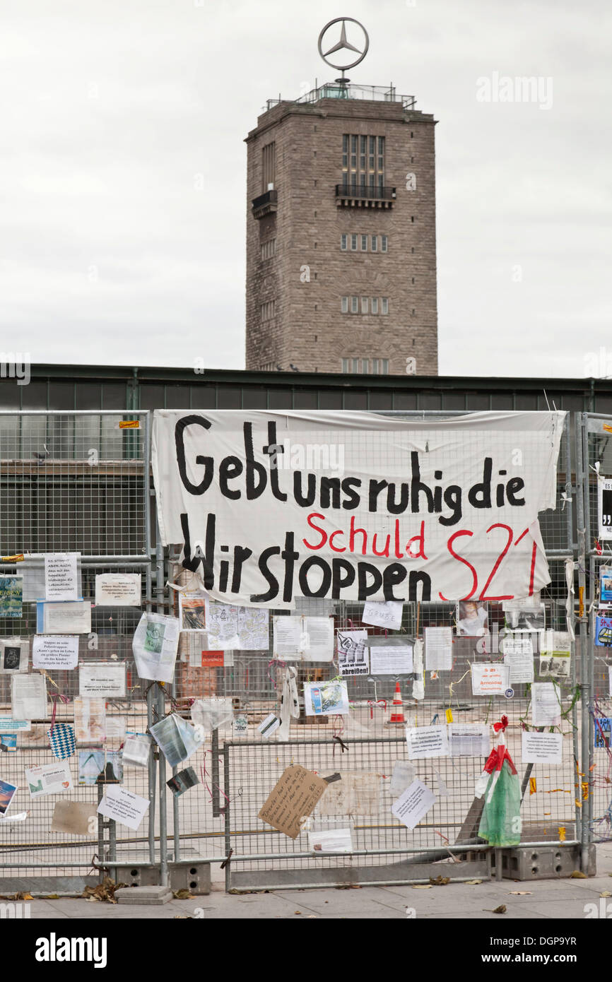 Protest posters against Stuttgart 21 railway project on a site fence, tower of the old railway station at back, Schlossgarten - Stock Image