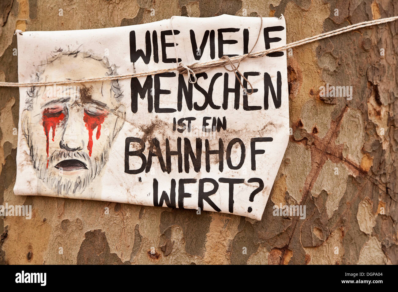 Protest poster 'Wie viele Menschen ist ein Bahnhof wert?', German for 'a train station is worth how many people?' on an old tree - Stock Image
