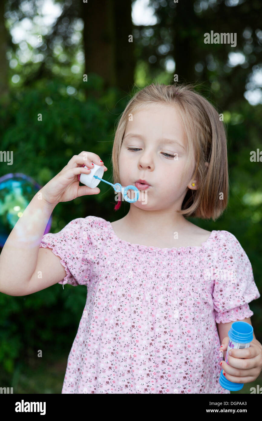 Girl, 4, blowing soap bubbles - Stock Image
