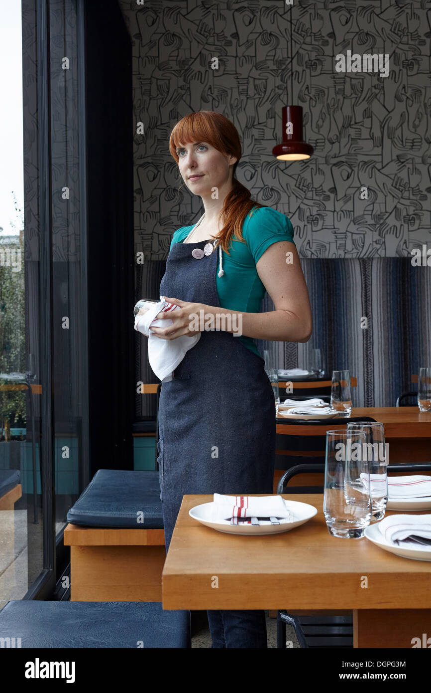 Mid adult woman polishing glass in restaurant - Stock Image