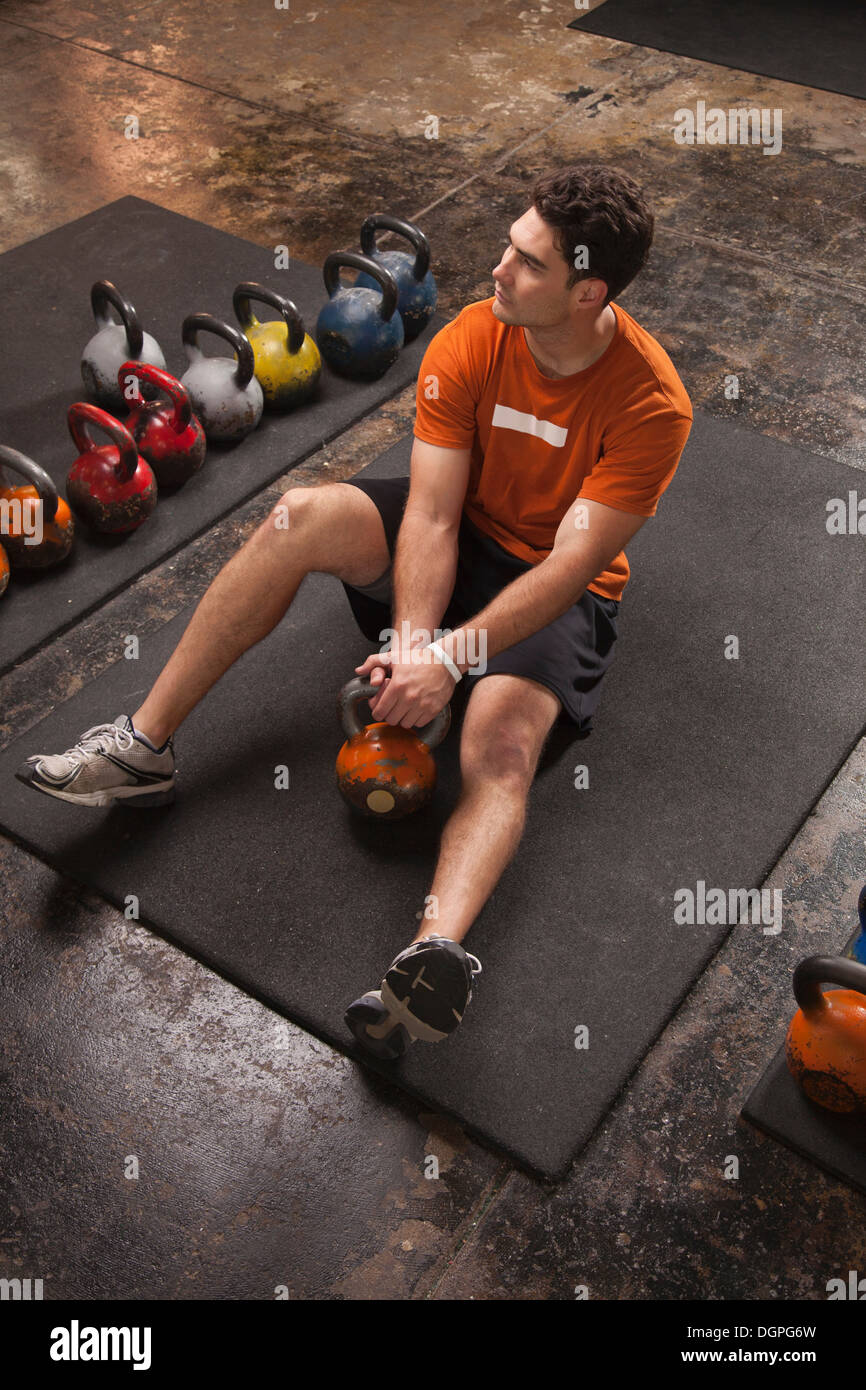 Bodybuilder resting on exercise mat in gym - Stock Image
