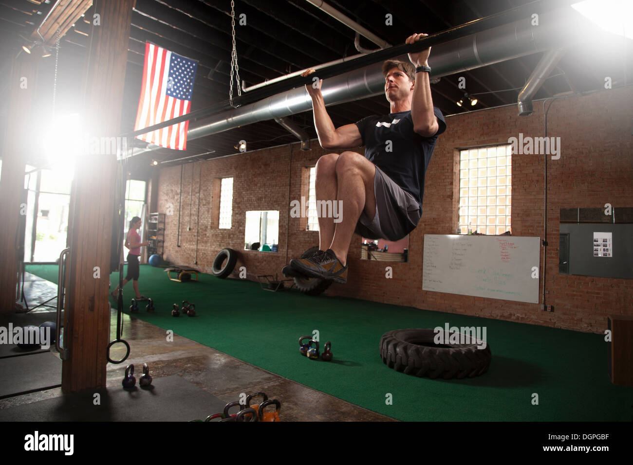 Bodybuilder doing pull up on bar in gym - Stock Image