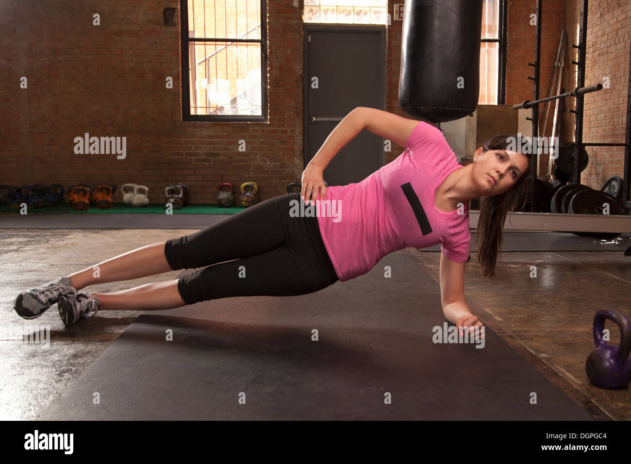 Young woman exercising on mat in gym - Stock Image