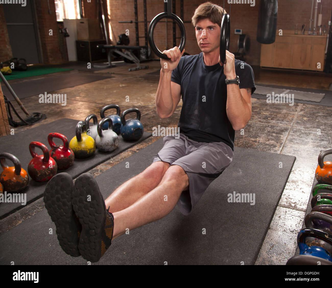 Bodybuilder on gym floor using rings - Stock Image
