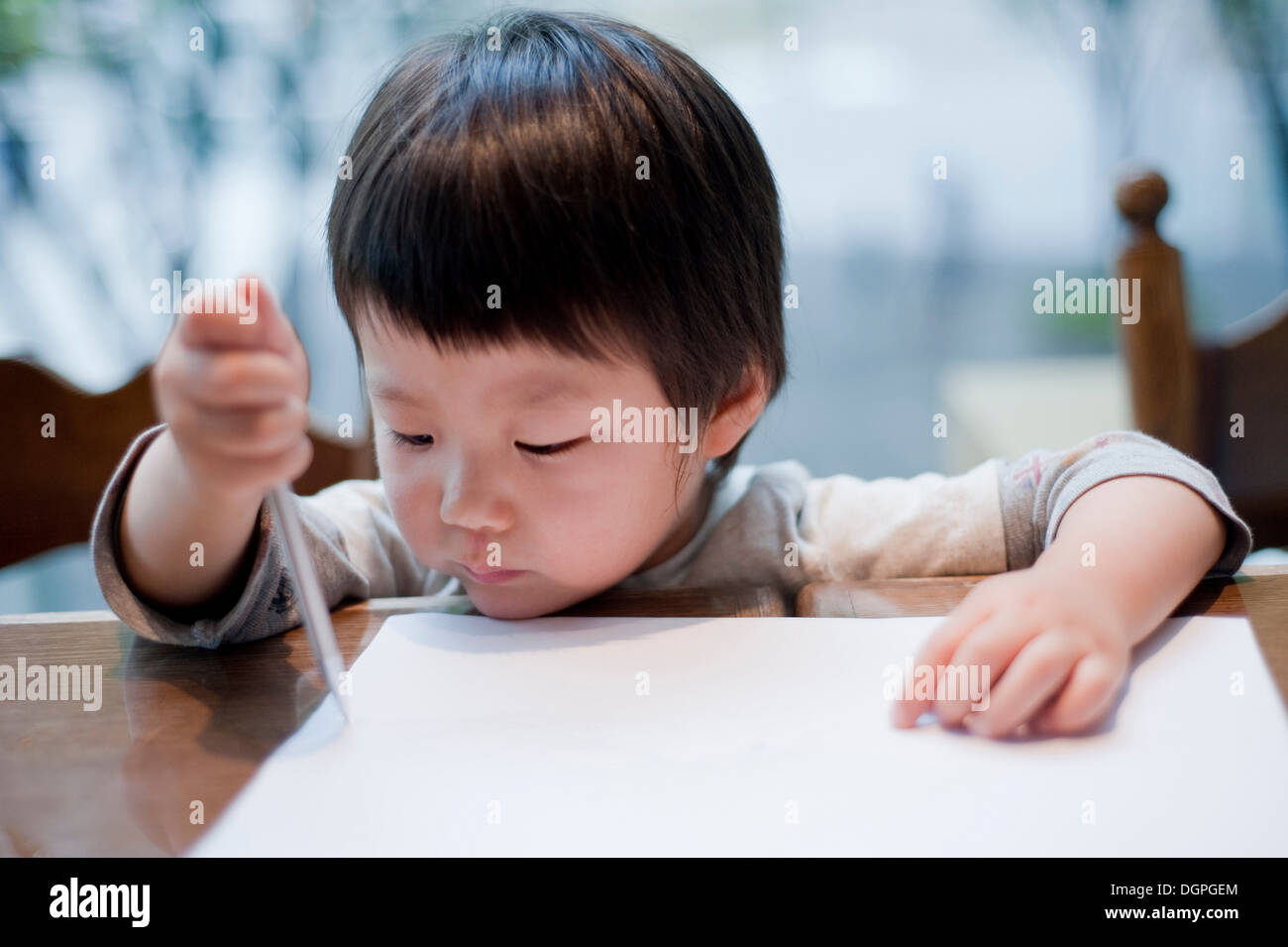Boy drawing on paper with pen, close up - Stock Image
