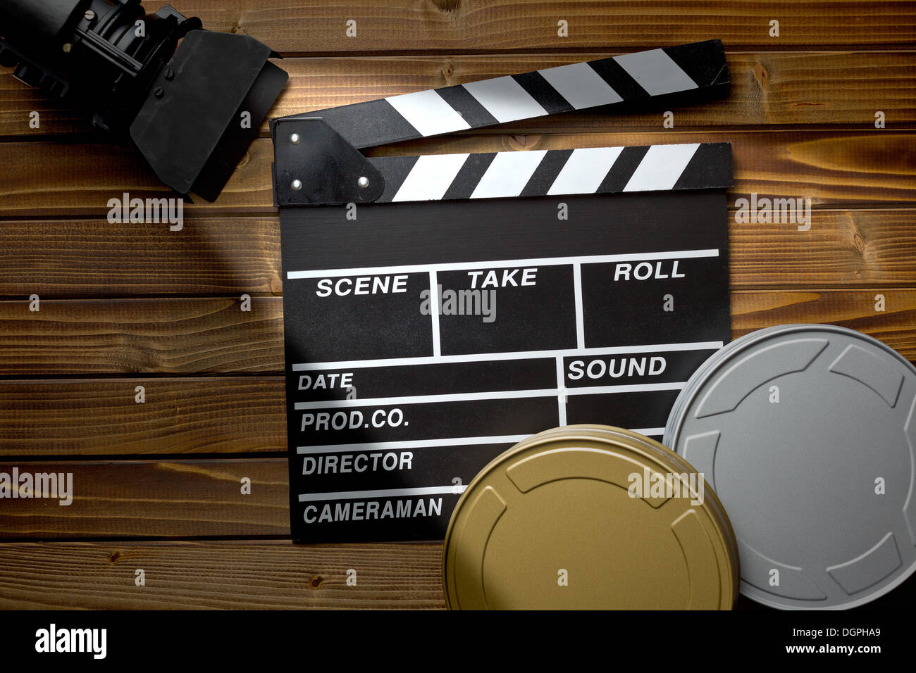 top view of clapper board with movie light and film reels on wooden table - Stock Image