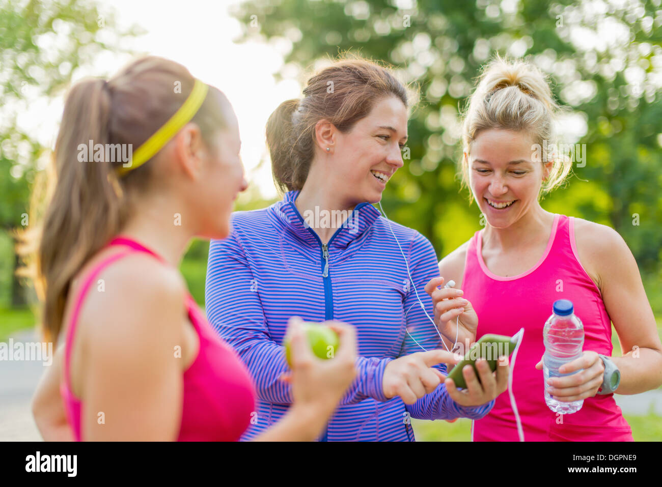 Group of happy active girls preparing for a run in nature by choosing music on a smart phone - Stock Image
