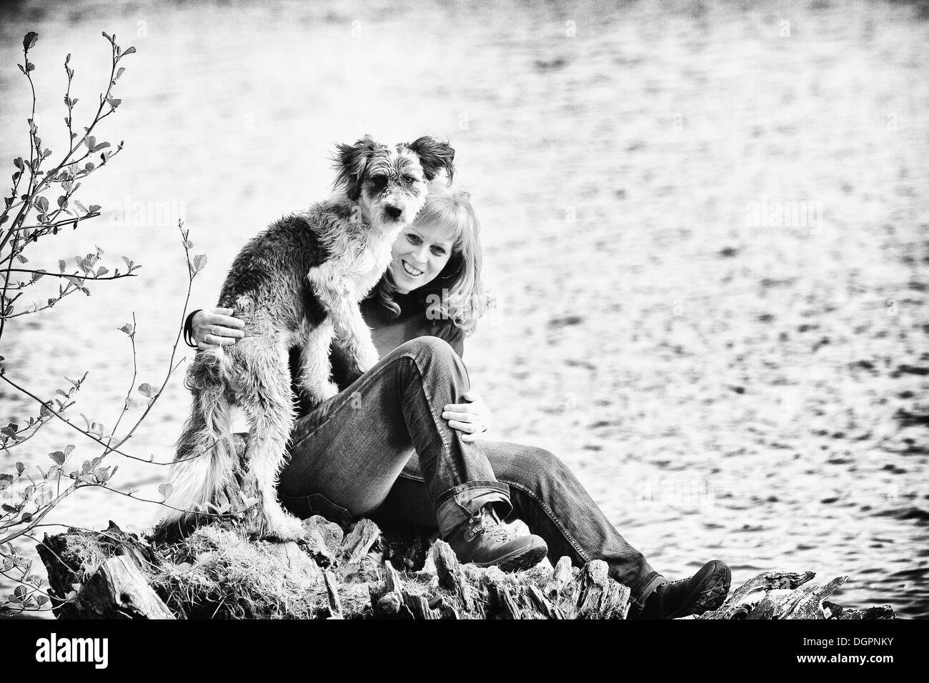 Woman sitting with her dog on a rock by a lake Stock Photo