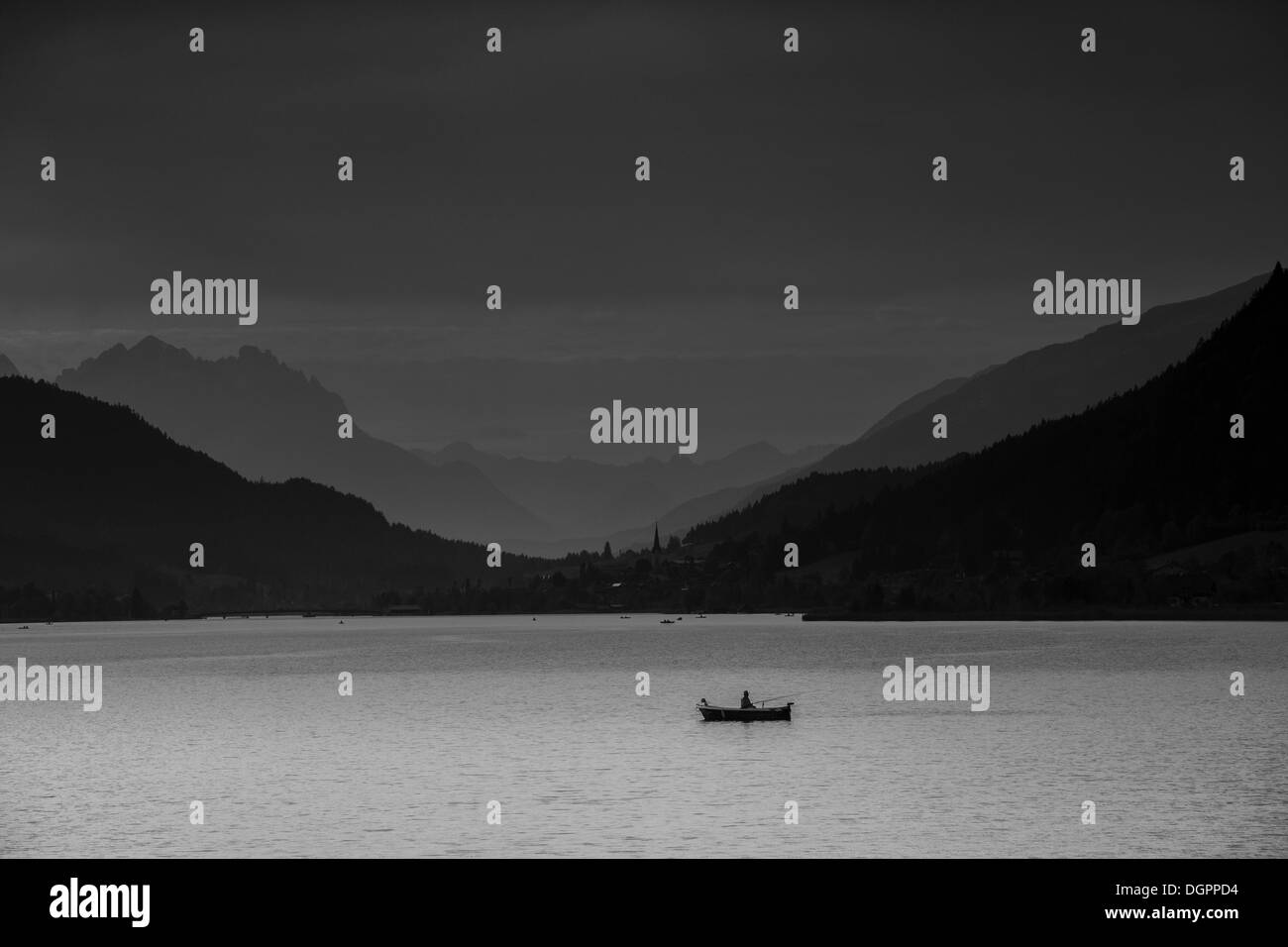 View over Weissensee lake towards Techendorf in the evening light, with a fisherman in a rowboat at the front, Weissensee lake - Stock Image