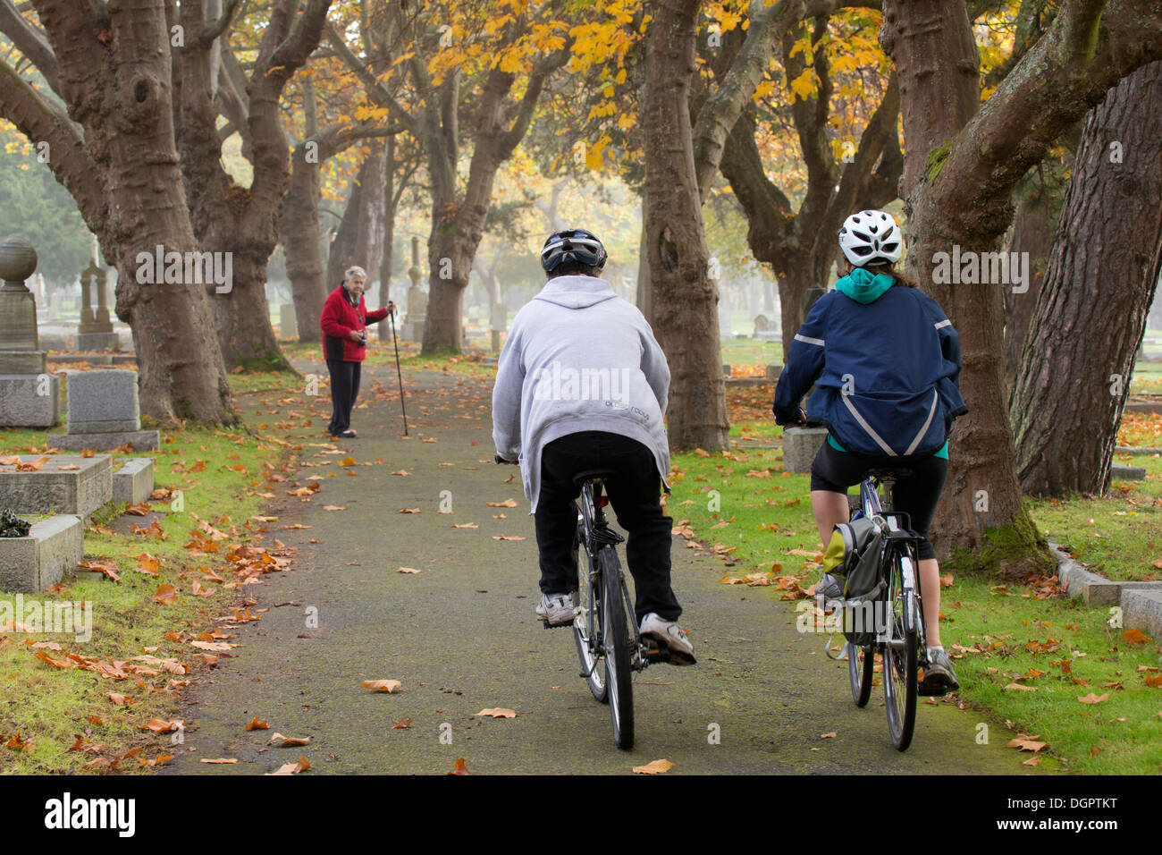 Bicyclists riding on path through Ross Bay cemetery in autumn -Victoria, British Columbia, Canada. - Stock Image