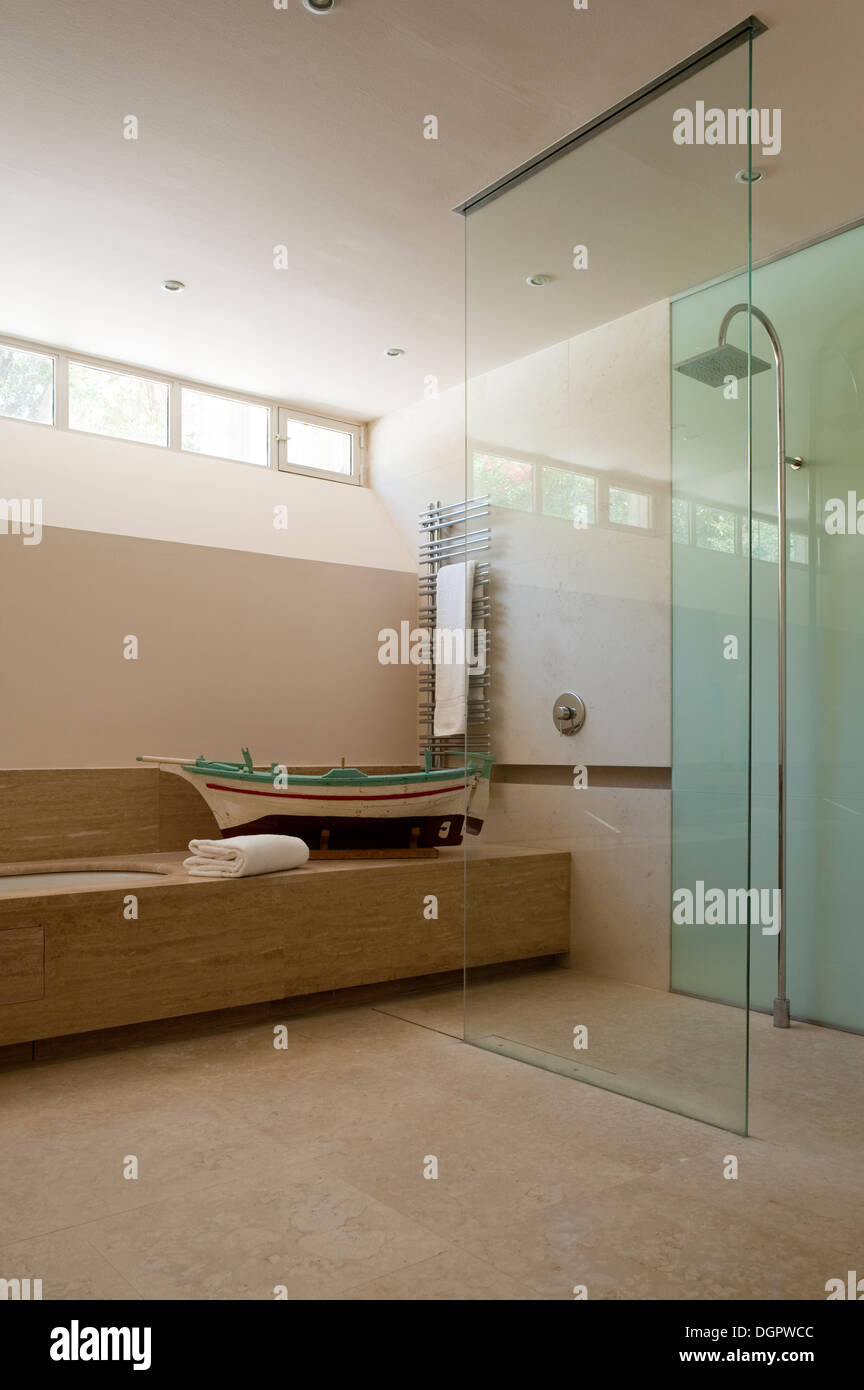 Glass shower enclosure in bathroom with wooden model fishing boat ...