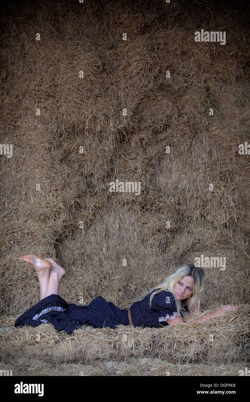 a blond woman is lying in the hay - Stock Image