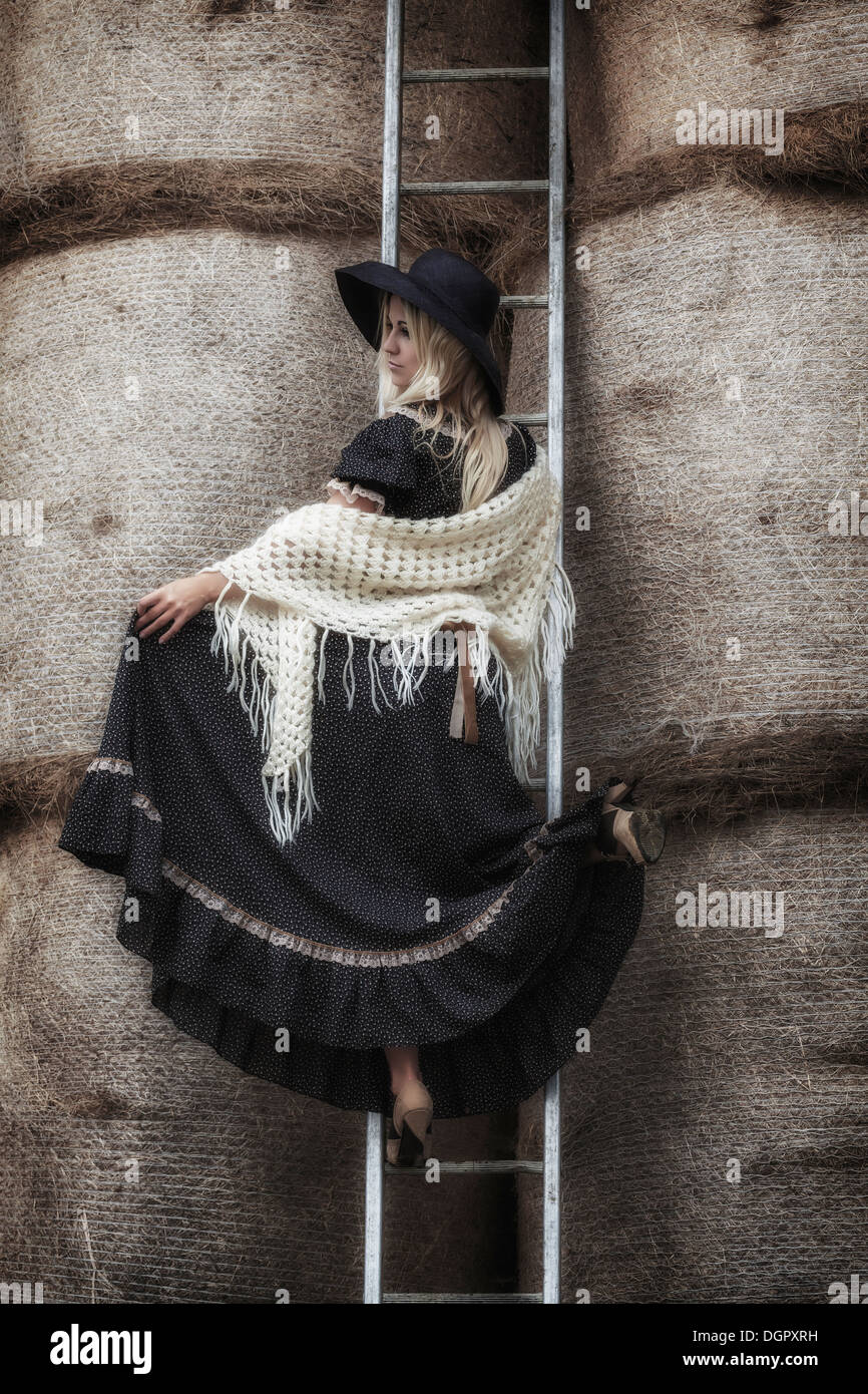 a beautiful girl on a ladder in a haystack - Stock Image
