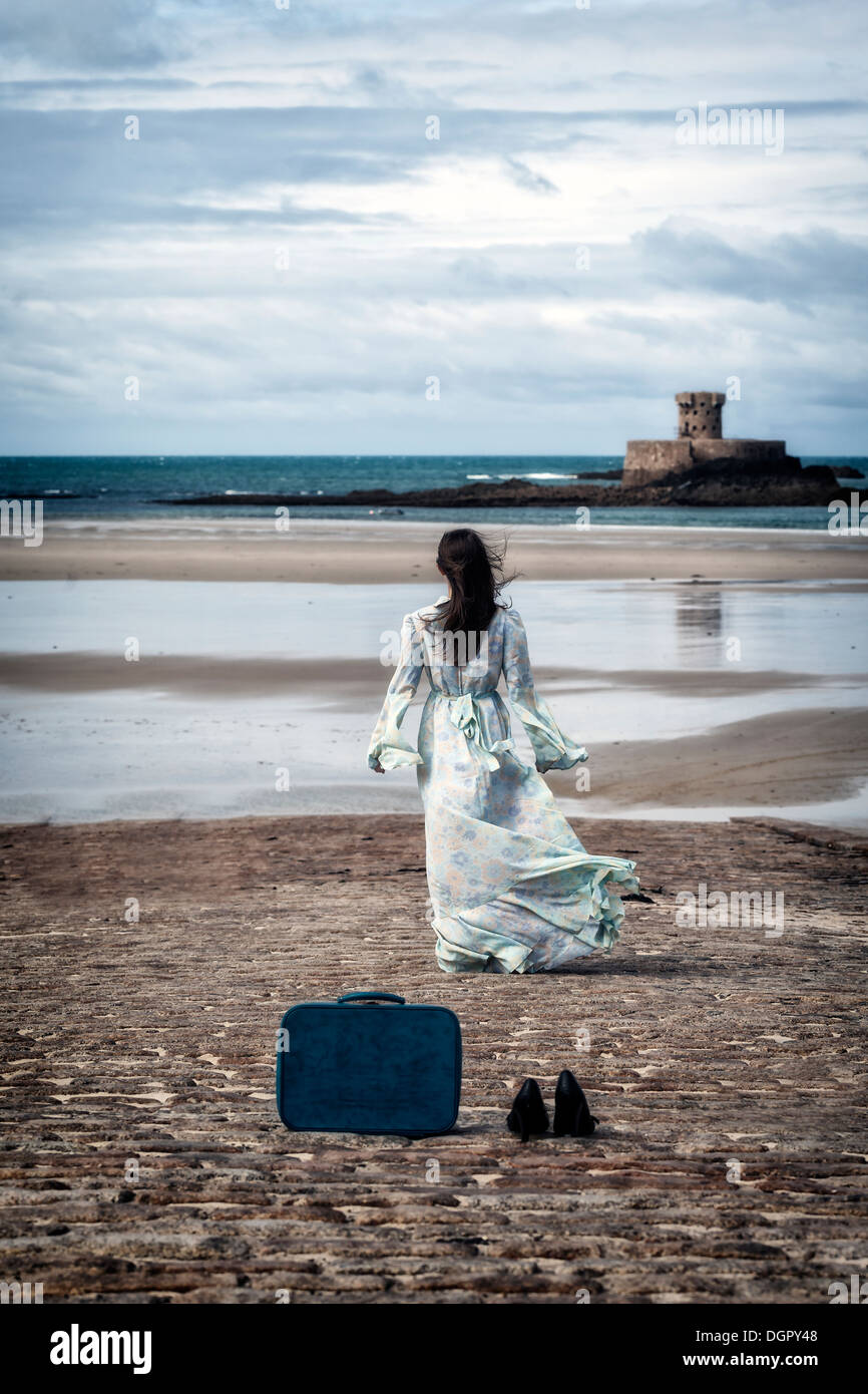 a woman in a floral dress is walking towards the sea, leaving her shoes and her suitcase behind her - Stock Image