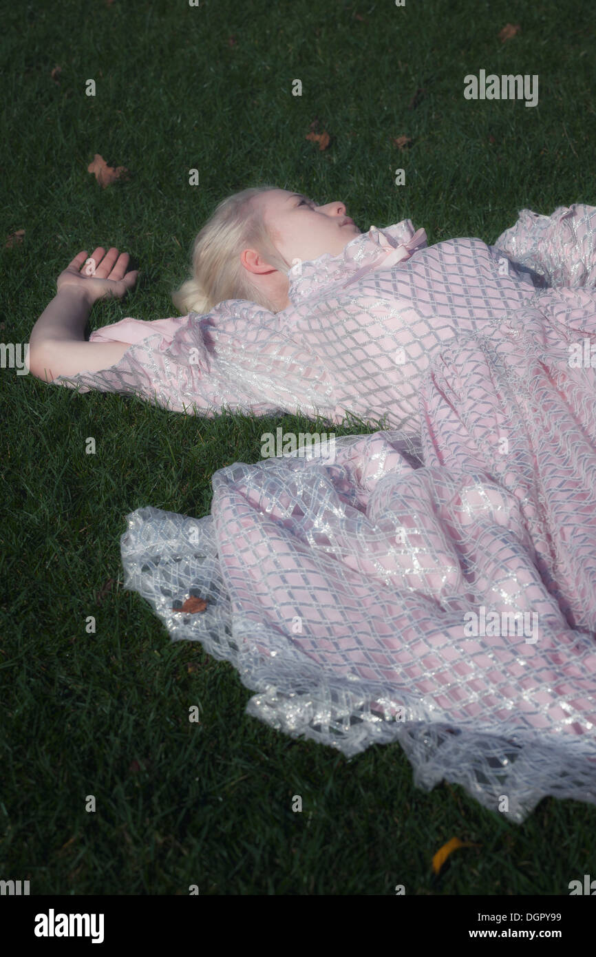 a woman in a period dress is lying in the grass - Stock Image