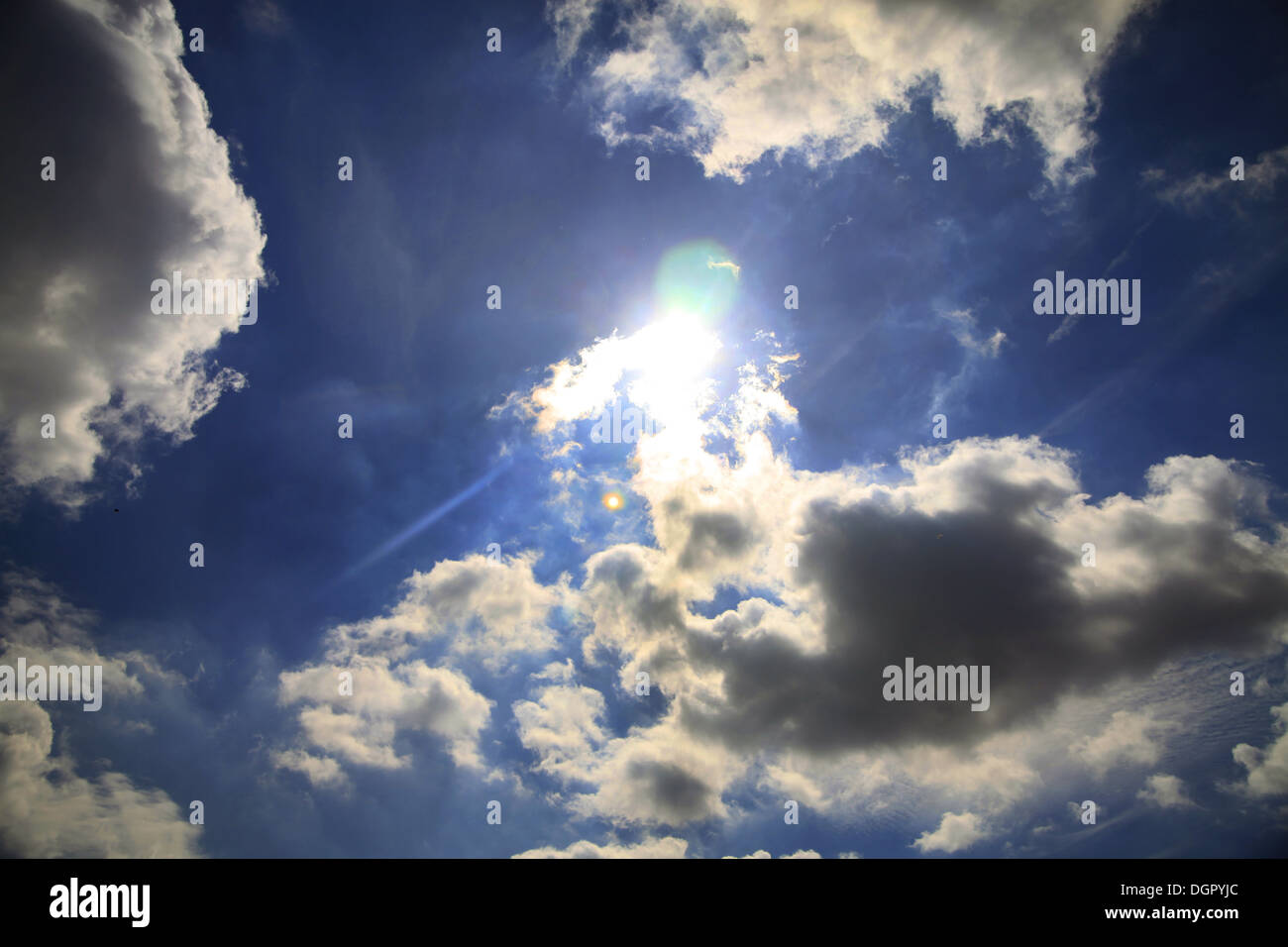 Sky with clouds, sun and lens flare. - Stock Image
