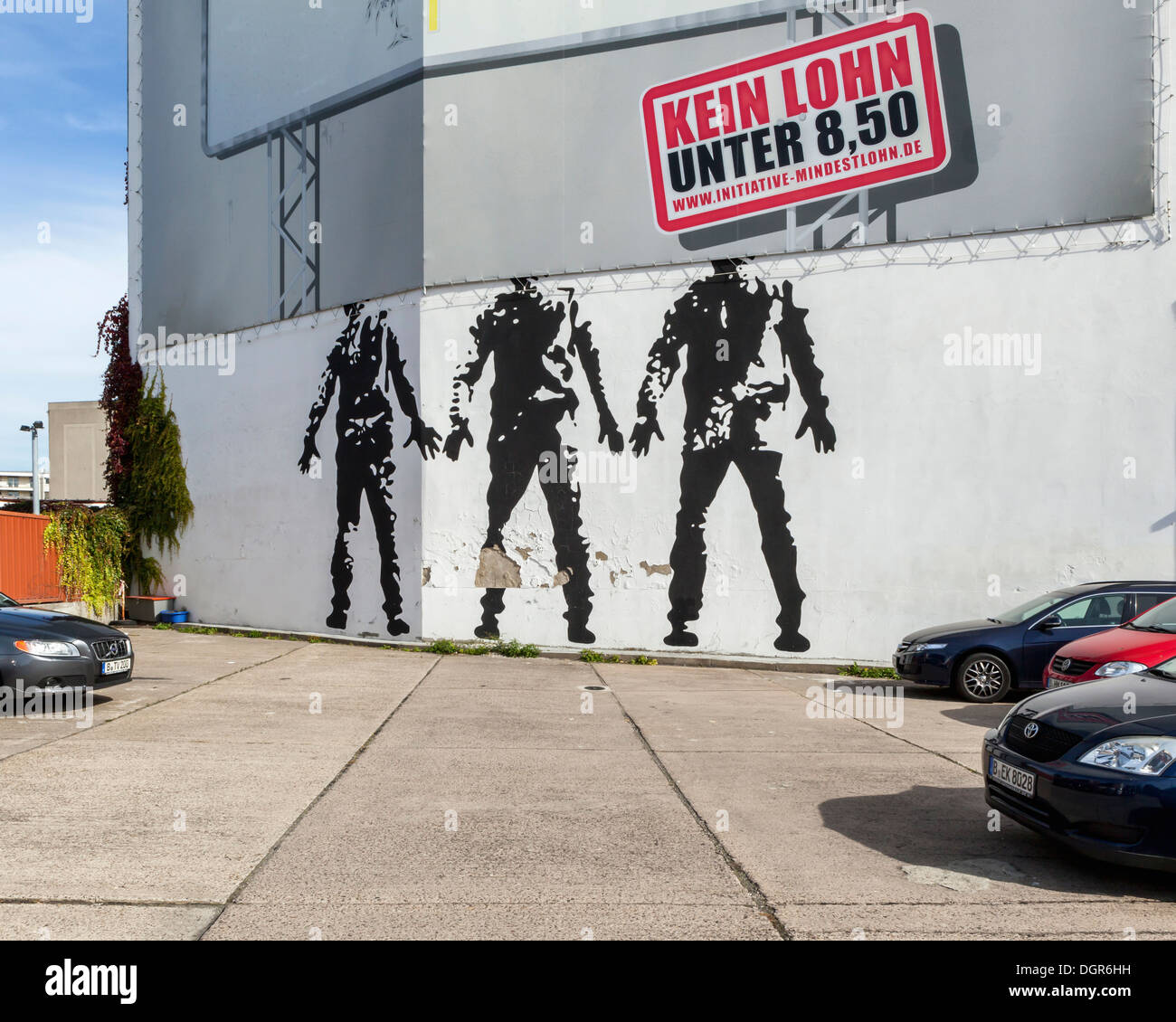 Political minimum wage poster 'No wage under 8.50 euros' and three headless men mural - Berlin - Stock Image