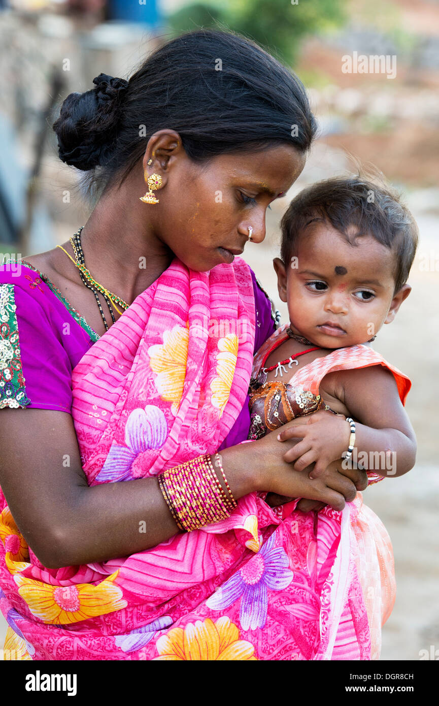 Young lower caste Indian teenage girl holding her baby ...