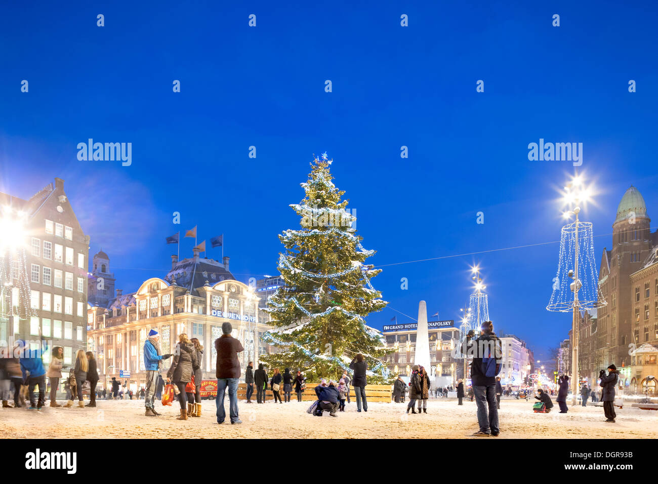 Amsterdam Christmas Tree w snow, Xmas lights in Dam Square with people, tourists, visitors, posing and taking pictures at dusk - Stock Image
