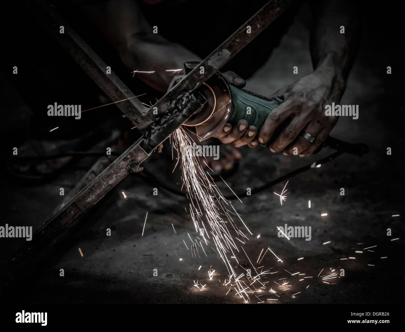 Sparks flying from a metalworker using a hand grinding power tool - Stock Image