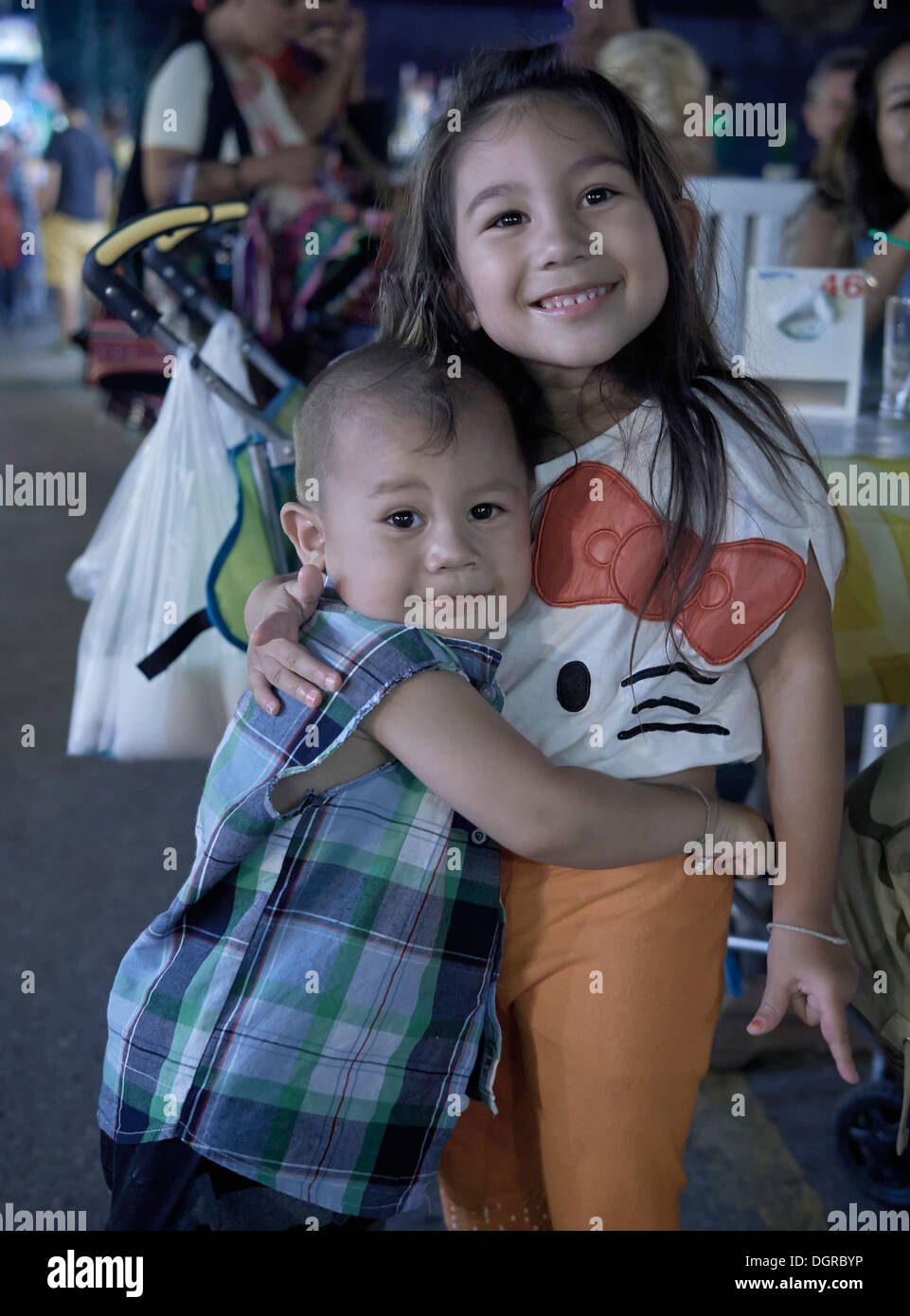 Cute kids hugging each other - brother and older sister. - Stock Image