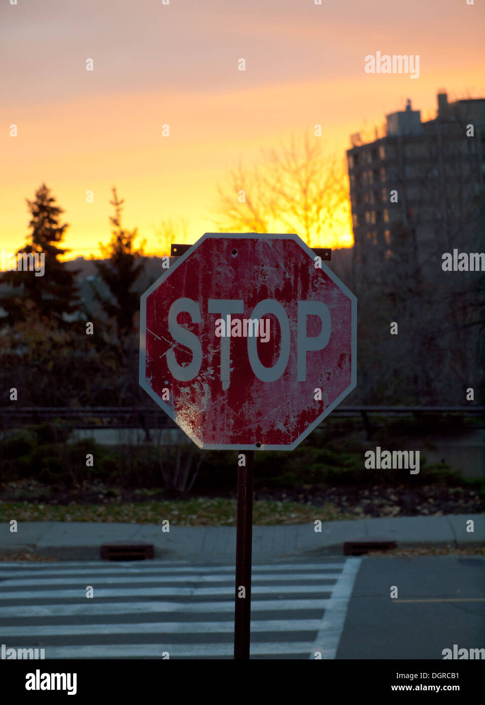An old, weathered stop sign at sunrise in Edmonton, Alberta, Canada. - Stock Image