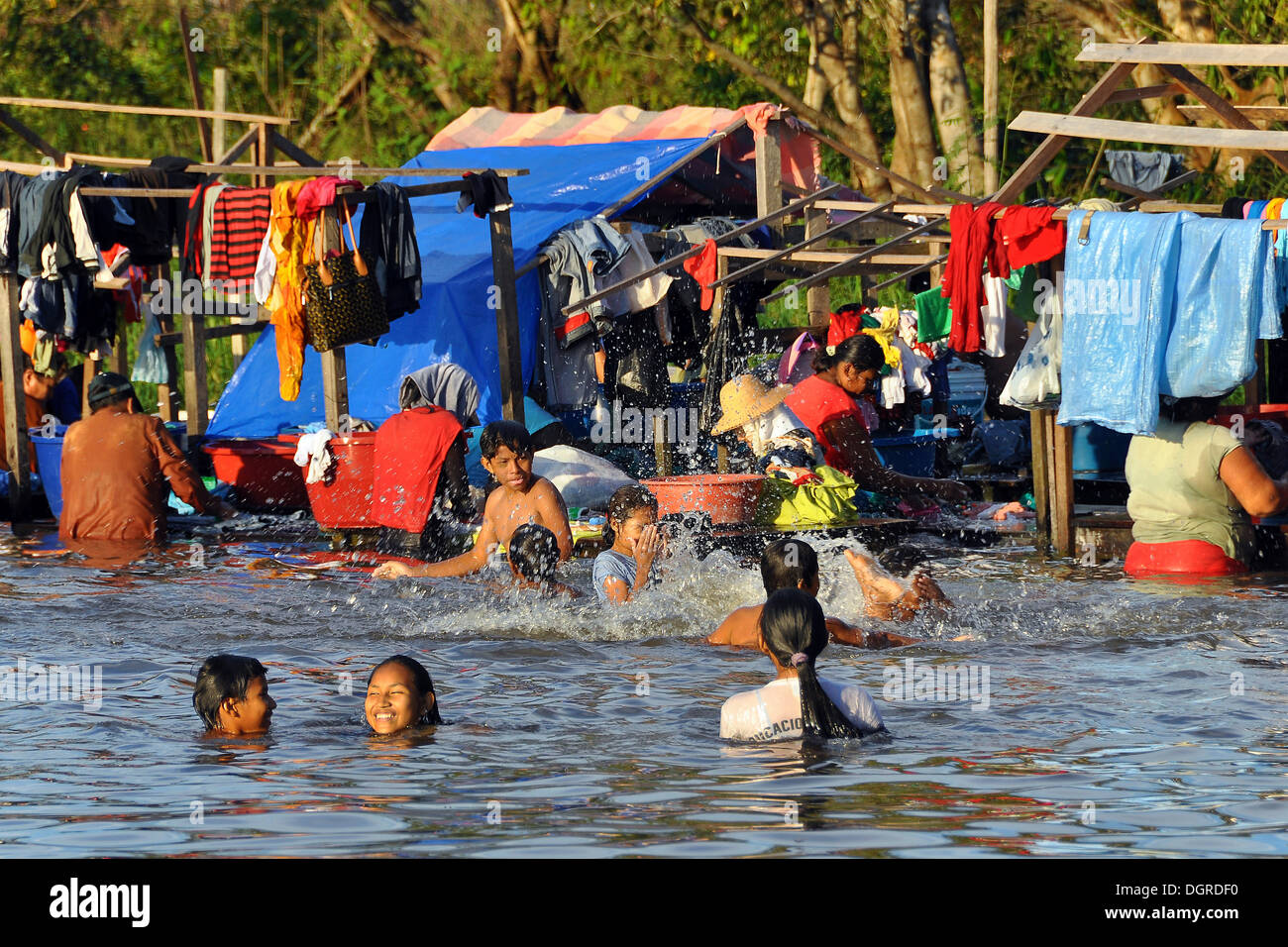 Children swimming in front of the laundry washing area in the river, Guayaramerín, Amazonia, Vaca Díez Province, Bolivia - Stock Image