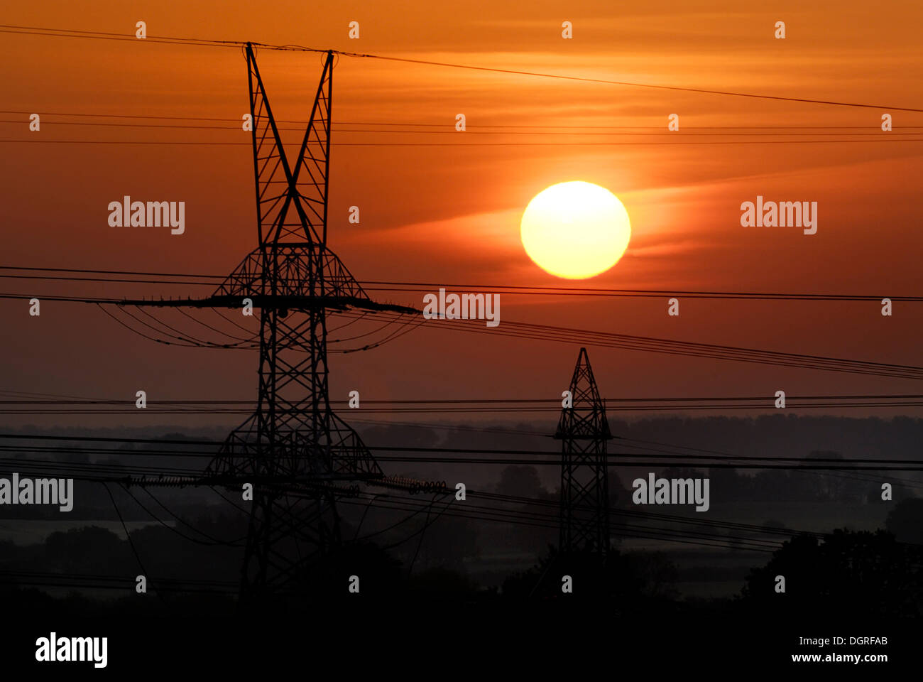 High-voltage transmission line in front of the rising sun, near Rendsburg, Schleswig-Holstein - Stock Image