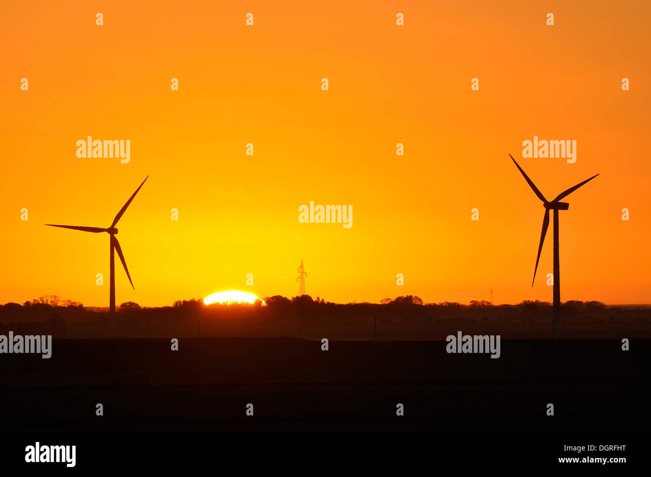 Nuclear dawn, wind power plant and transmission line in front of a sunrise, Eiderstedt, Schleswig-Holstein - Stock Image