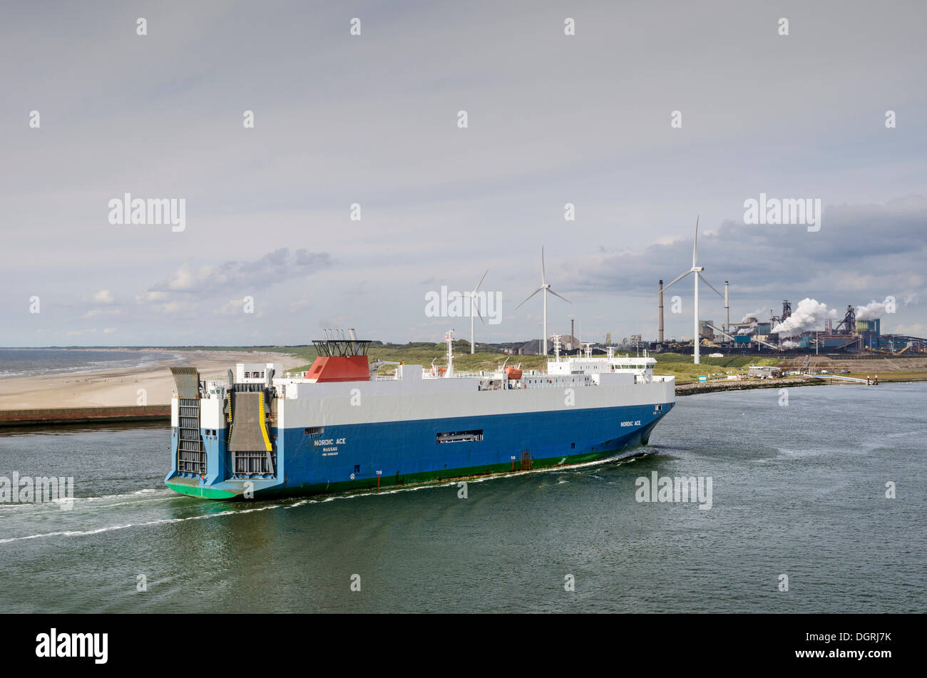 Nordic Ace car ferry approaching the port of Ijmuiden, wind turbines and industrial facilities at the back, North Holland - Stock Image