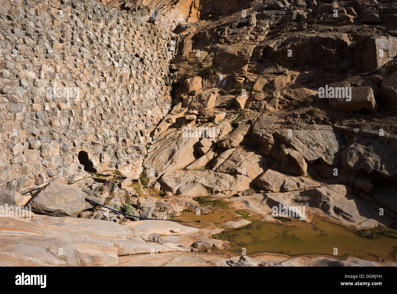The dam of Presa de las Penitas, made of syenite rock from the nearby intrusion, in Barranco de las Penitas, Vega de Rio Palmas - Stock Image