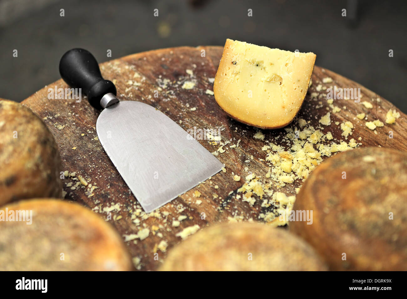 Special knife and famous italian cheese pecorino on small wooden table. - Stock Image