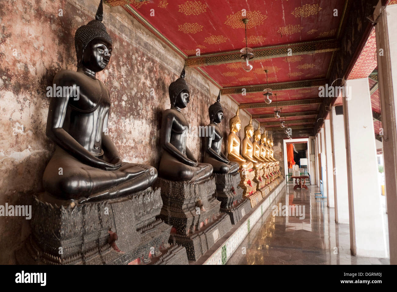 Black Buddha statues, gilded through donations, Buddhist temple, Wat Suthat, Bangkok, Thailand, Southeast Asia, Asia - Stock Image