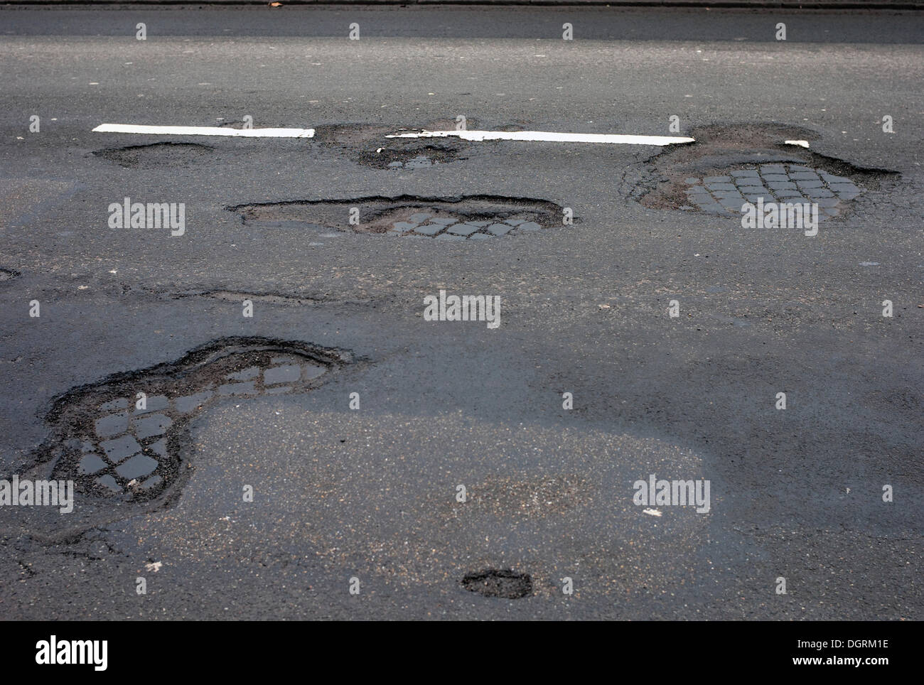 Frost damage, potholes in the road surface, Germany - Stock Image