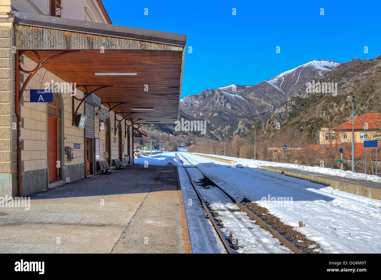 Rails covered with snow along empty platform on small railway station in the mountains. - Stock Image