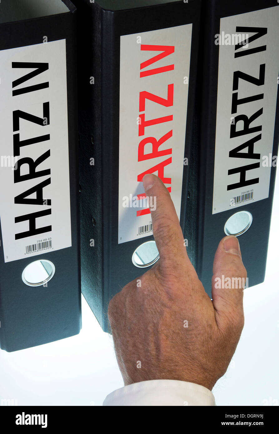 Hand pointing to a ring binder labeled Hartz IV, German term for long-term unemployment benefits, symbolic image - Stock Image