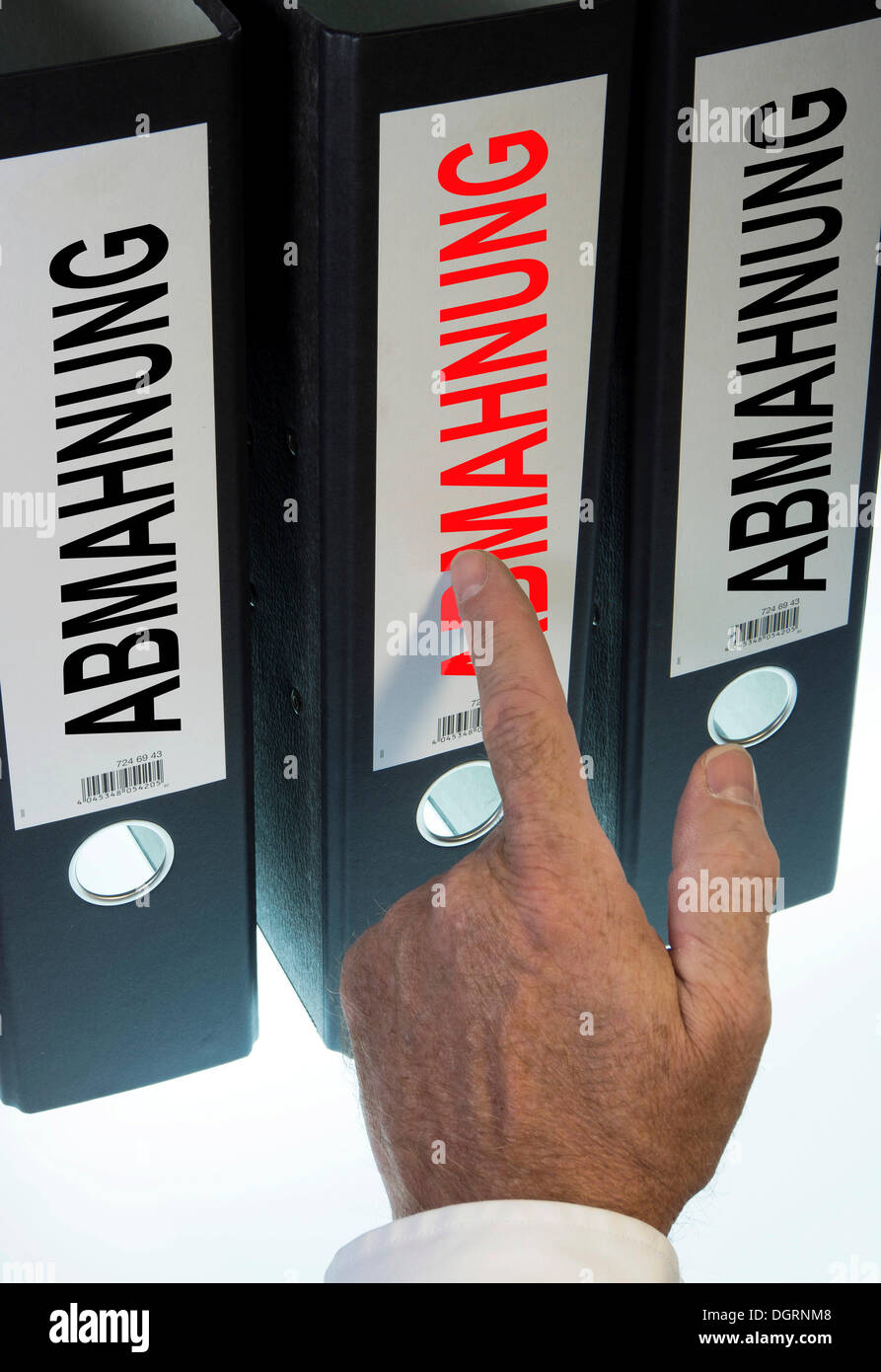 Hand pointing to a ring binder labelled 'ABMAHNUNG', German for 'warning letter' - Stock Image