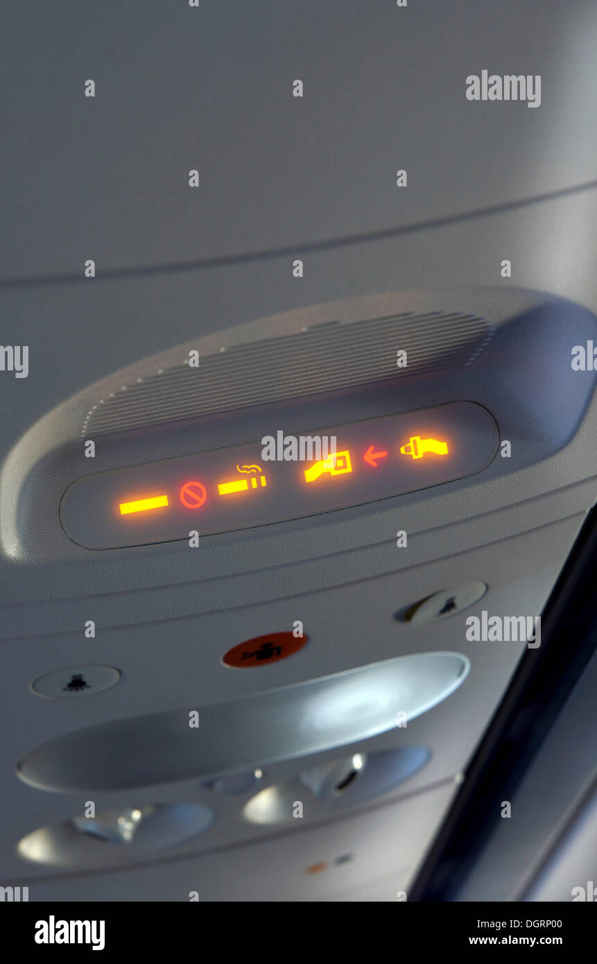 Seatbelt and non-smoking-indicator on an airplane, in flight - Stock Image