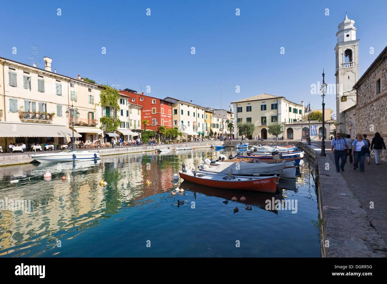 Boats anchored in the harbour along Via Fontana street, Lazise, Lago di Garda, Lake Garda, Lombardy, Italy, Europe - Stock Image