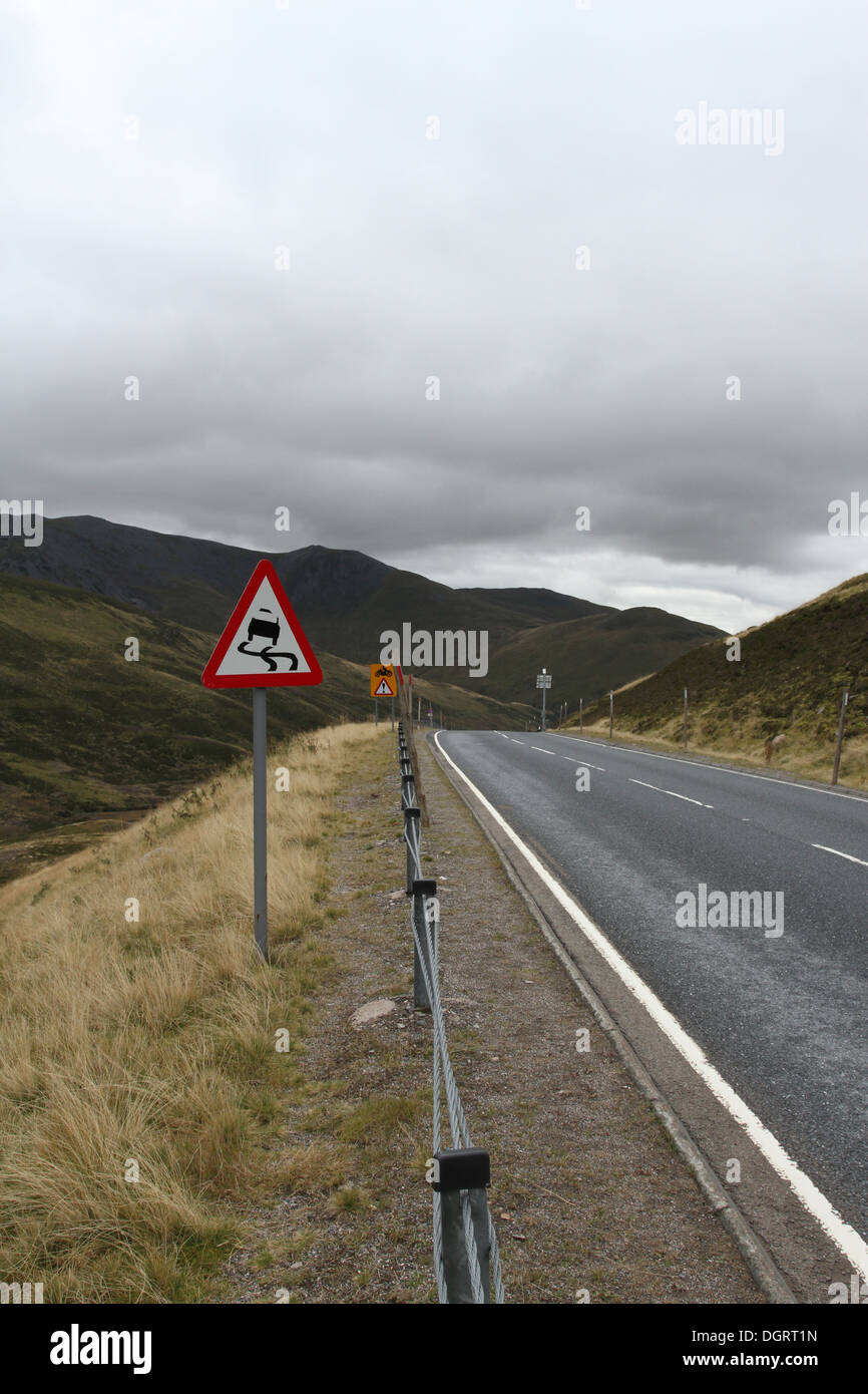 Warning of slippery road sign on steep hill A93 Scotland October 2013 - Stock Image