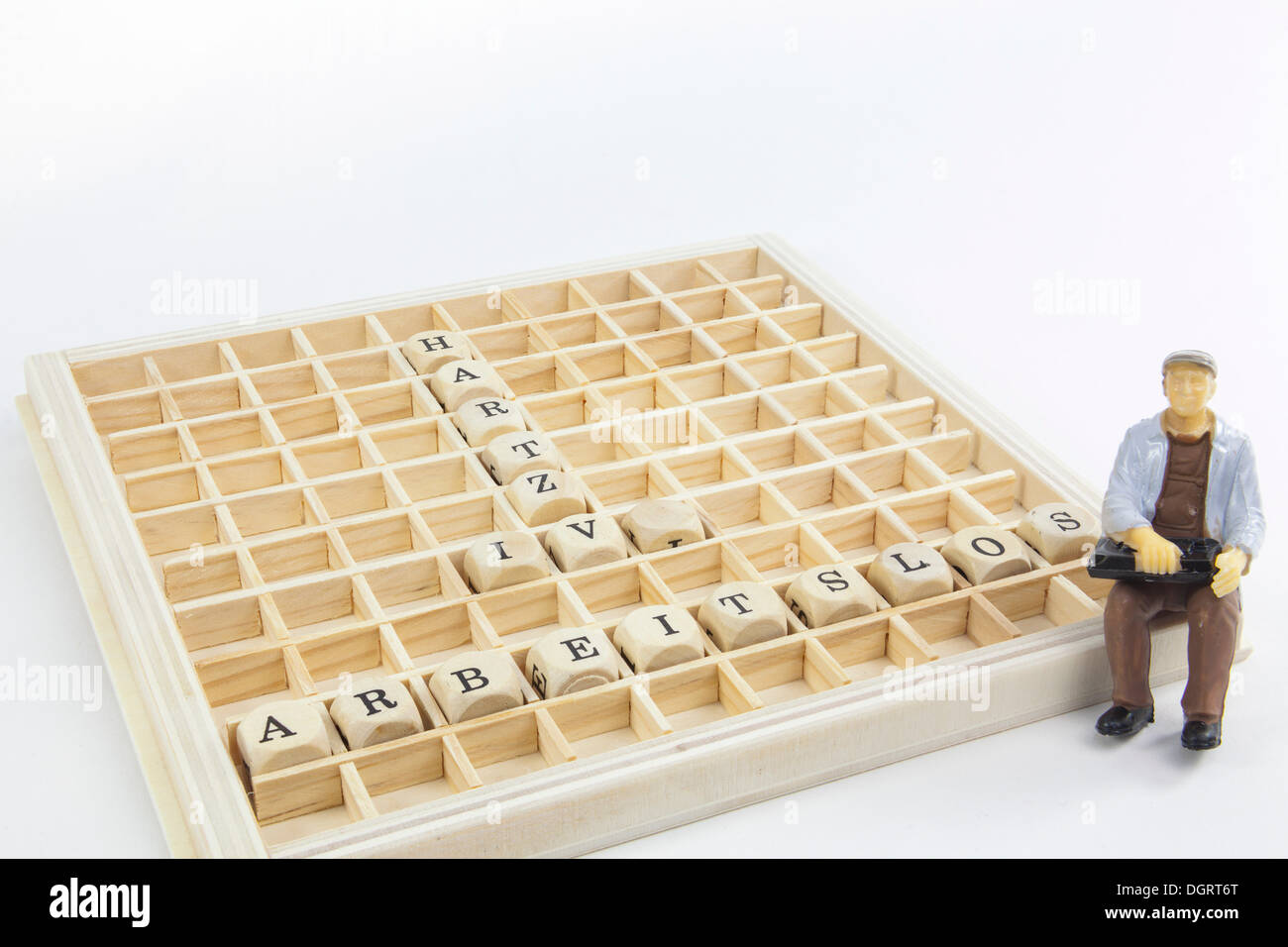 Miniature figure of an unemployed worker, letter cubes forming the words 'arbeitslos' and 'Hartz IV', German for 'unemployed' - Stock Image